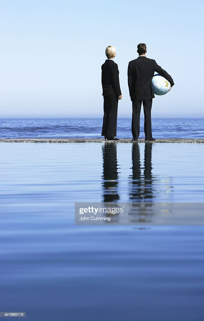Businessman and Businesswoman Standing Side by Side Looking at the Sea : Stock Photo