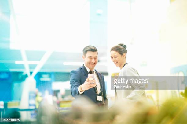 Businessman and businesswoman standing together, looking at smartphone, laughing