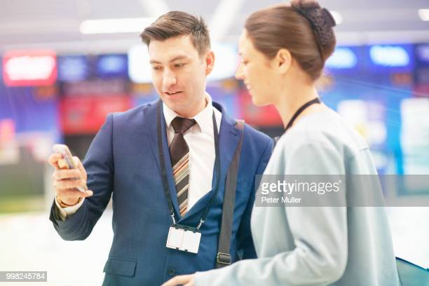 Businessman and businesswoman standing together, looking at smartphone