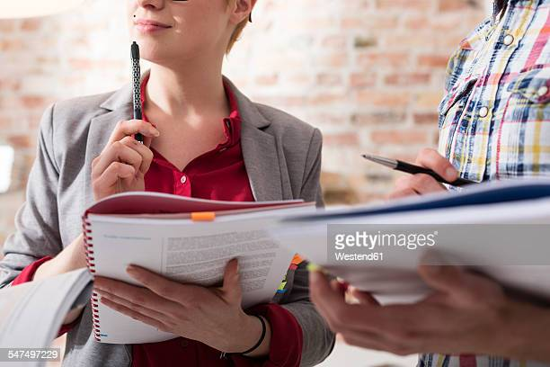 Businessman and businesswoman taking notes in office