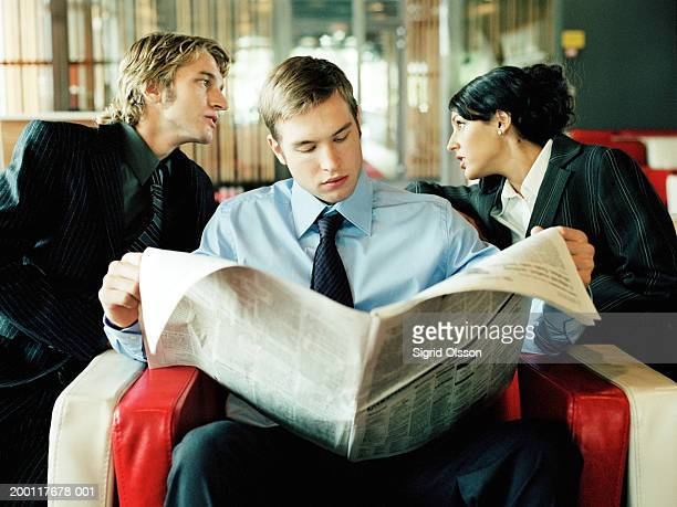 businessman and businesswoman talking behind man reading newspaper - rumor stock pictures, royalty-free photos & images