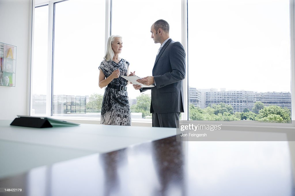 A businessman and businesswoman talking by window : Stock Photo