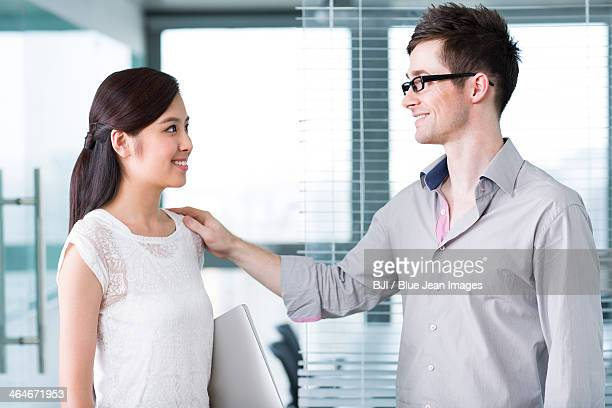 Businessman and businesswoman talking happily