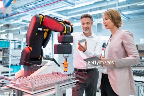 businessman and businesswoman talking in a modern factory hall - robotic arm stock pictures, royalty-free photos & images