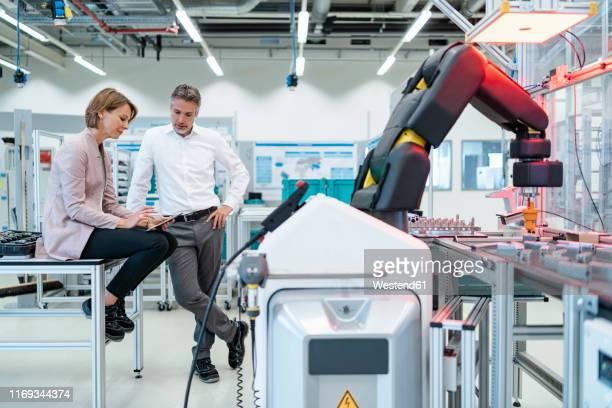 businessman and businesswoman talking in a modern factory hall - ingenieurwesen stock-fotos und bilder