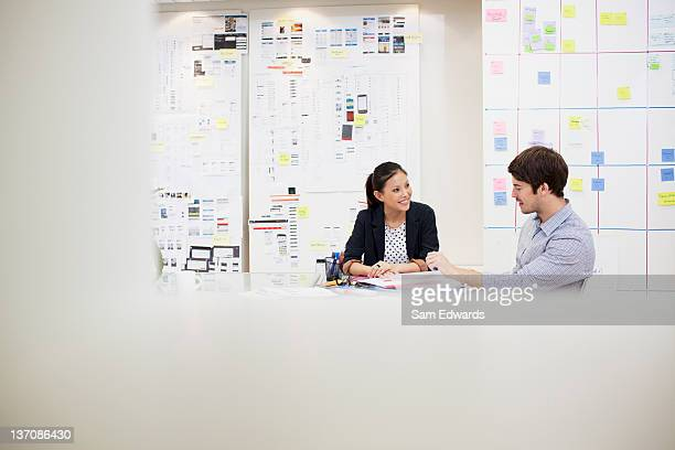 businessman and businesswoman talking in meeting - focus on background stock pictures, royalty-free photos & images