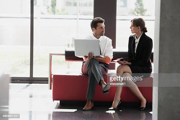 Businessman and businesswoman talking in office lobby