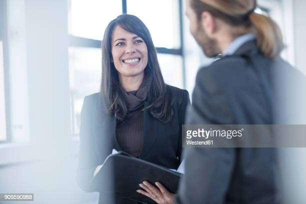 businessman and businesswoman talking in office - work romance stock pictures, royalty-free photos & images