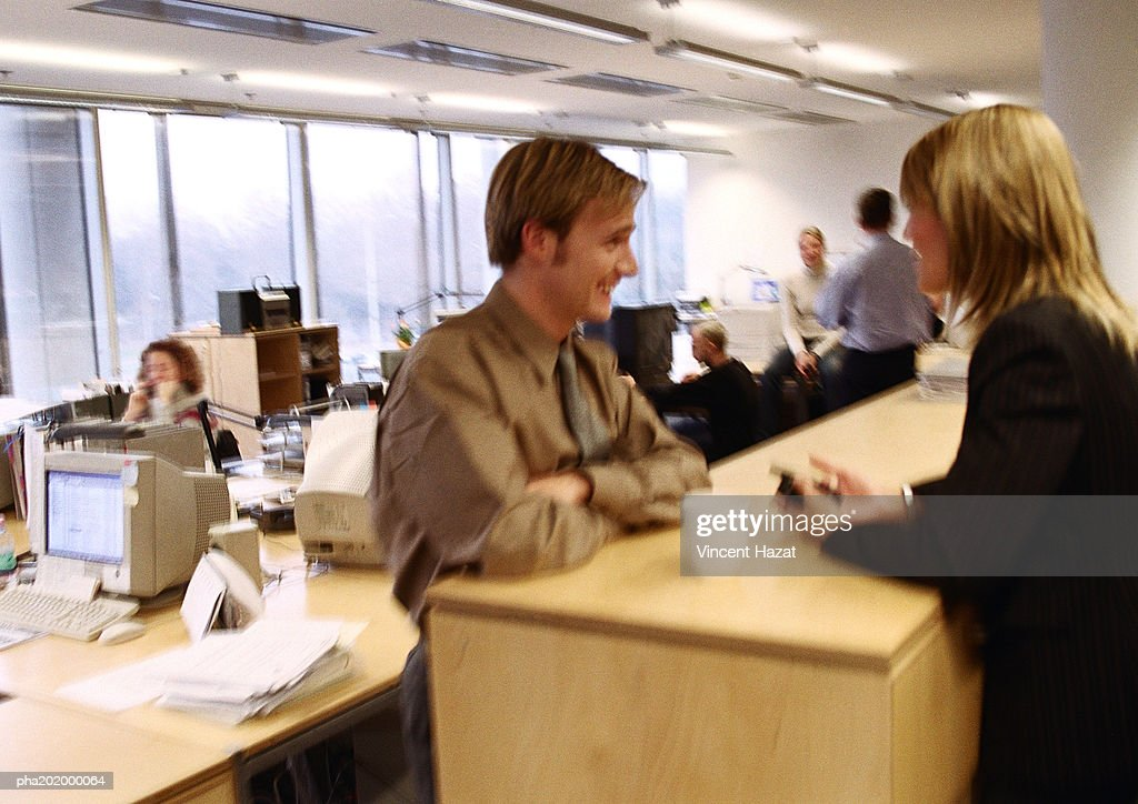 Businessman and businesswoman talking in office. : Stock Photo