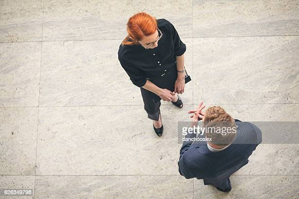 Businessman and businesswoman talking in the lobby overhead shot