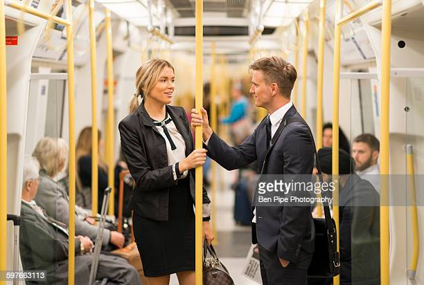 Businessman and businesswoman talking in tube, London Underground, UK