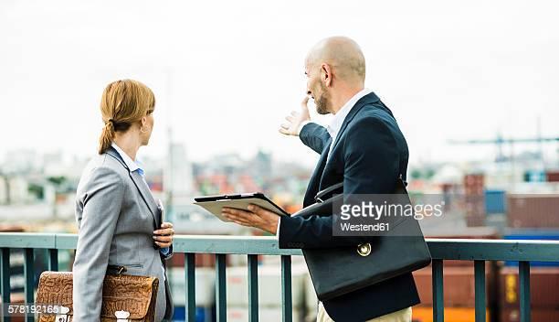 Businessman and businesswoman talking on bridge