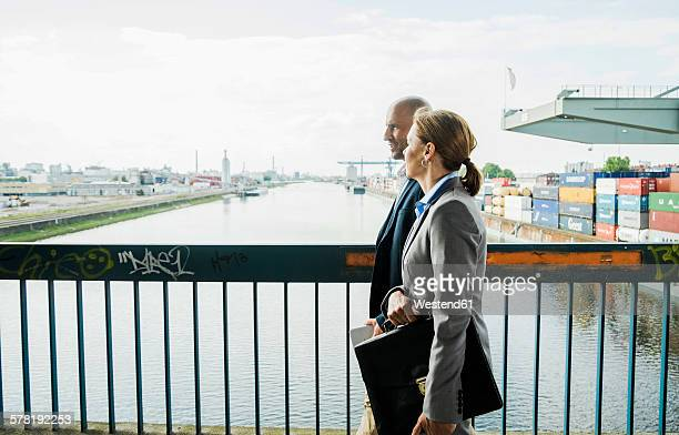 Businessman and businesswoman talking on bridge