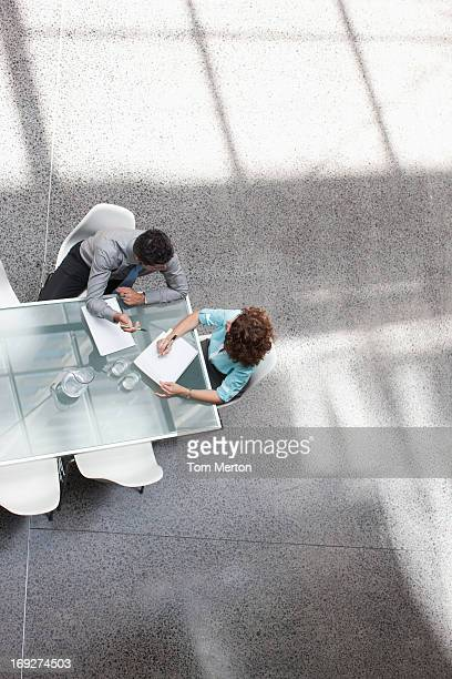 Businessman and businesswoman talking on conference table