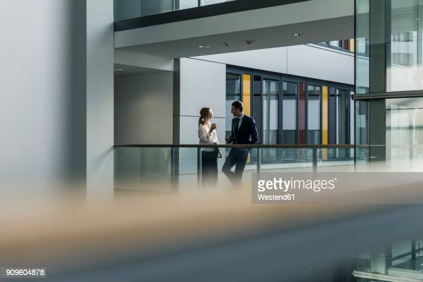 Businessman and businesswoman talking on office floor
