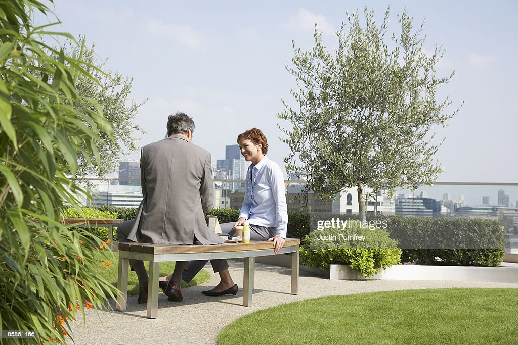 Businessman and businesswoman talking on rooftop : Stock-Foto