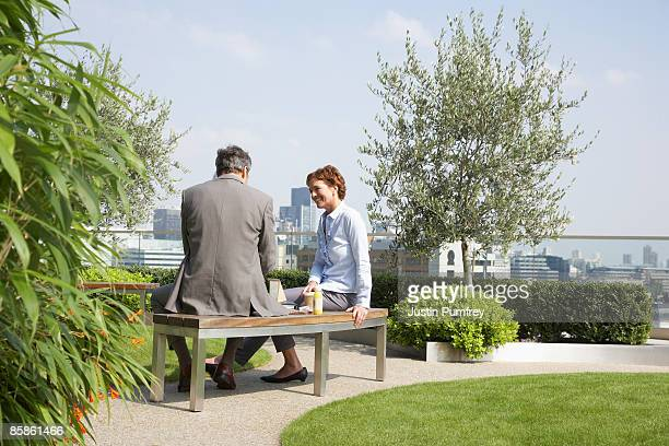 businessman and businesswoman talking on rooftop - bench stock pictures, royalty-free photos & images