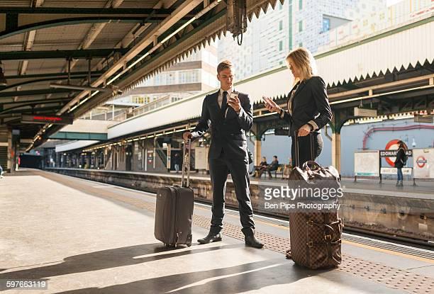 businessman and businesswoman texting on platform, underground station, london, uk - vertical red tube fotografías e imágenes de stock