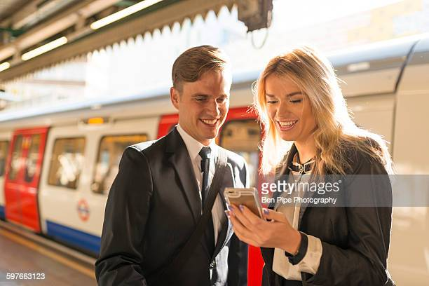 Businessman and businesswoman texting on platform, Underground station, London, UK