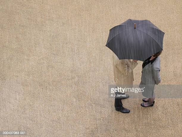businessman and businesswoman under umbrella in rain, overhead view - under skirt stock photos and pictures