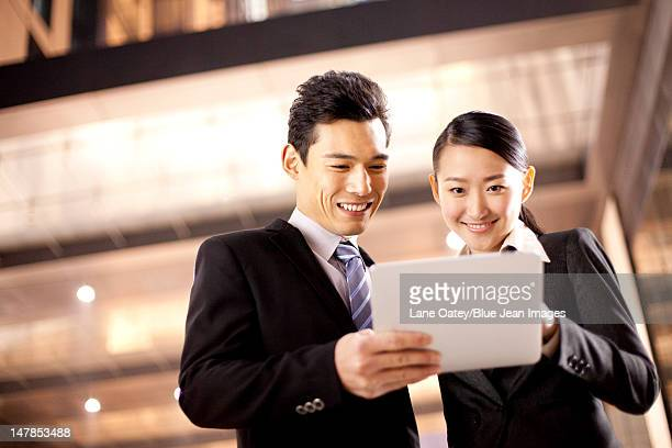A businessman and businesswoman using a digital tablet outside an office building at night