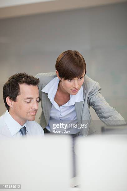 Businessman and businesswoman using computer at desk