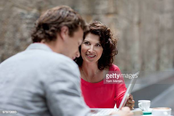Businessman and businesswoman using laptop at table