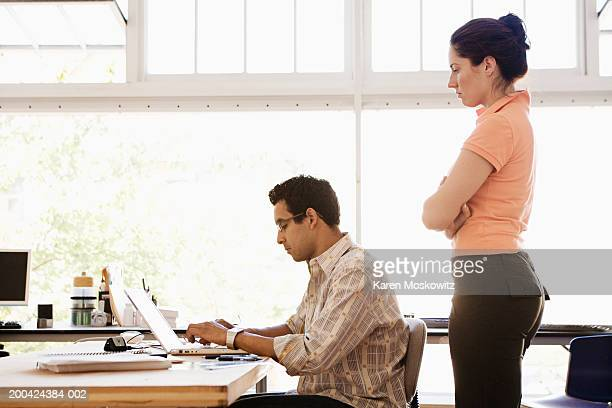 Businessman and businesswoman using laptop in office, side view