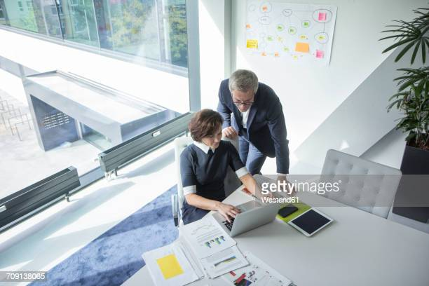 Businessman and businesswoman using laptop in office together