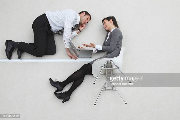 Businessman and woman using laptop in air, elevated view