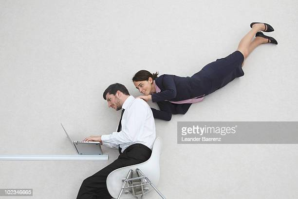 Businessman and woman flying, using laptop, elevated view