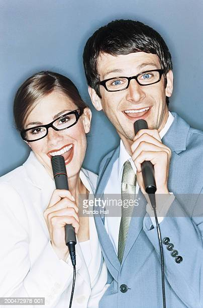 Businessman and businesswoman using microphones, smiling, portrait