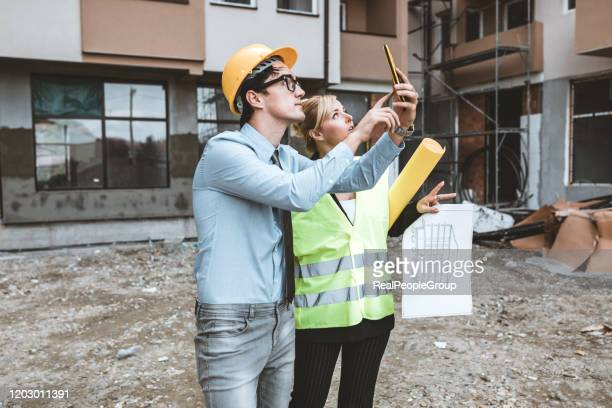 businessman and businesswoman using see plan paper at construction site - real estate developer stock pictures, royalty-free photos & images