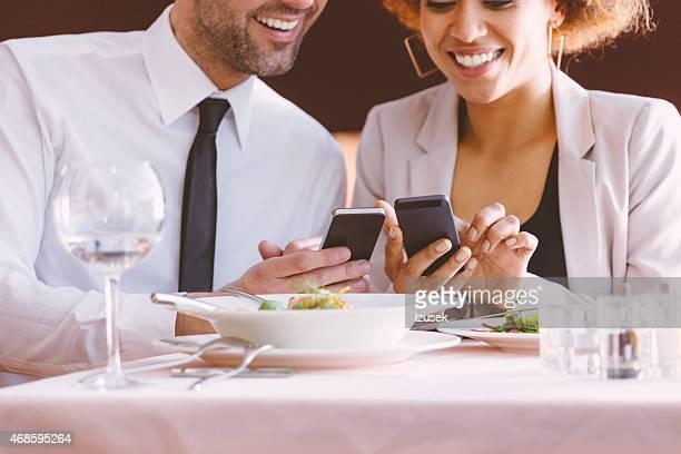 Homme d'affaires et Femme d'affaires à l'aide de téléphone intelligent à déjeuner
