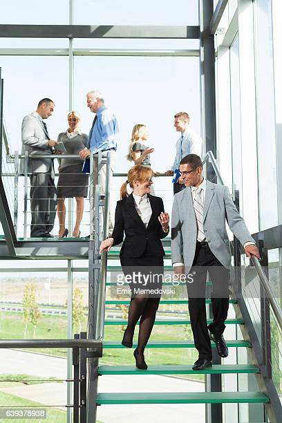 Businessman and businesswoman walking down stairs and communicating