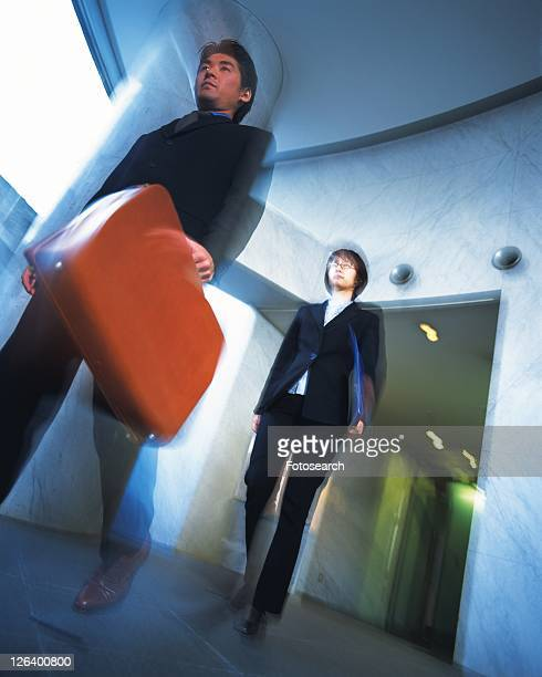 businessman and businesswoman walking down the hallway, portrait, low angle view, blurred motion - low angle view photos et images de collection