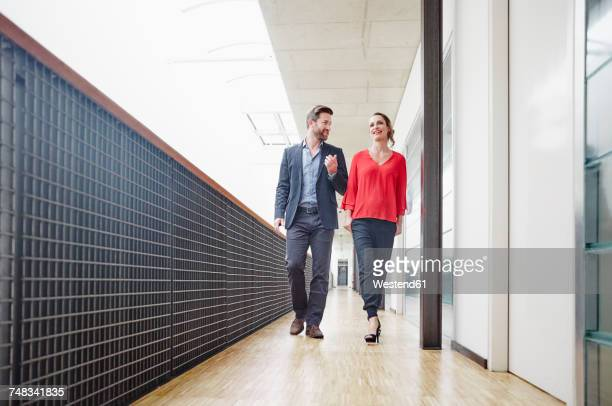 Businessman and businesswoman walking on office floor