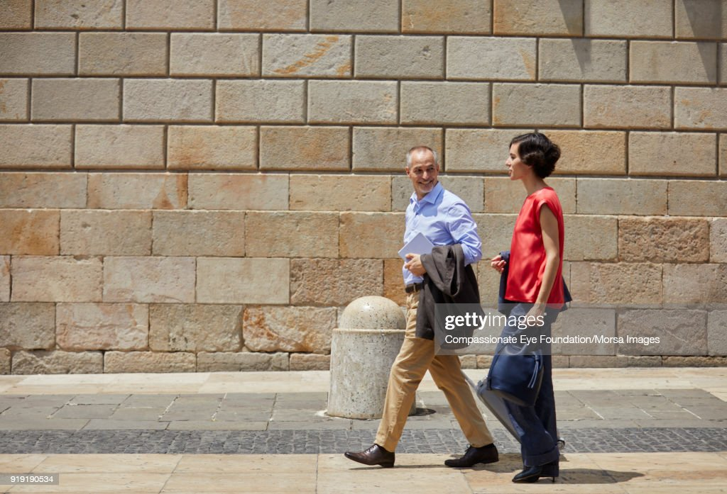 Businessman and businesswoman walking on street in Barcelona : Stock Photo