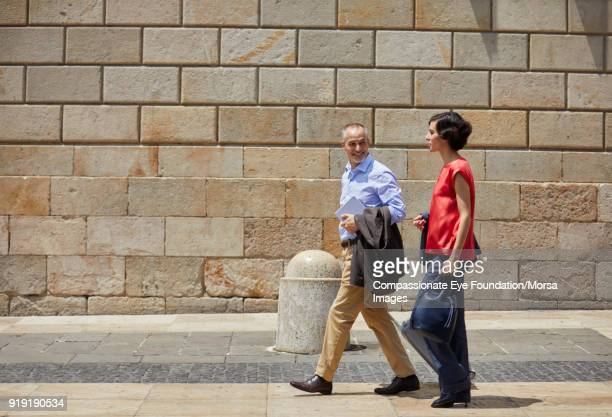 businessman and businesswoman walking on street in barcelona - red pants stock pictures, royalty-free photos & images