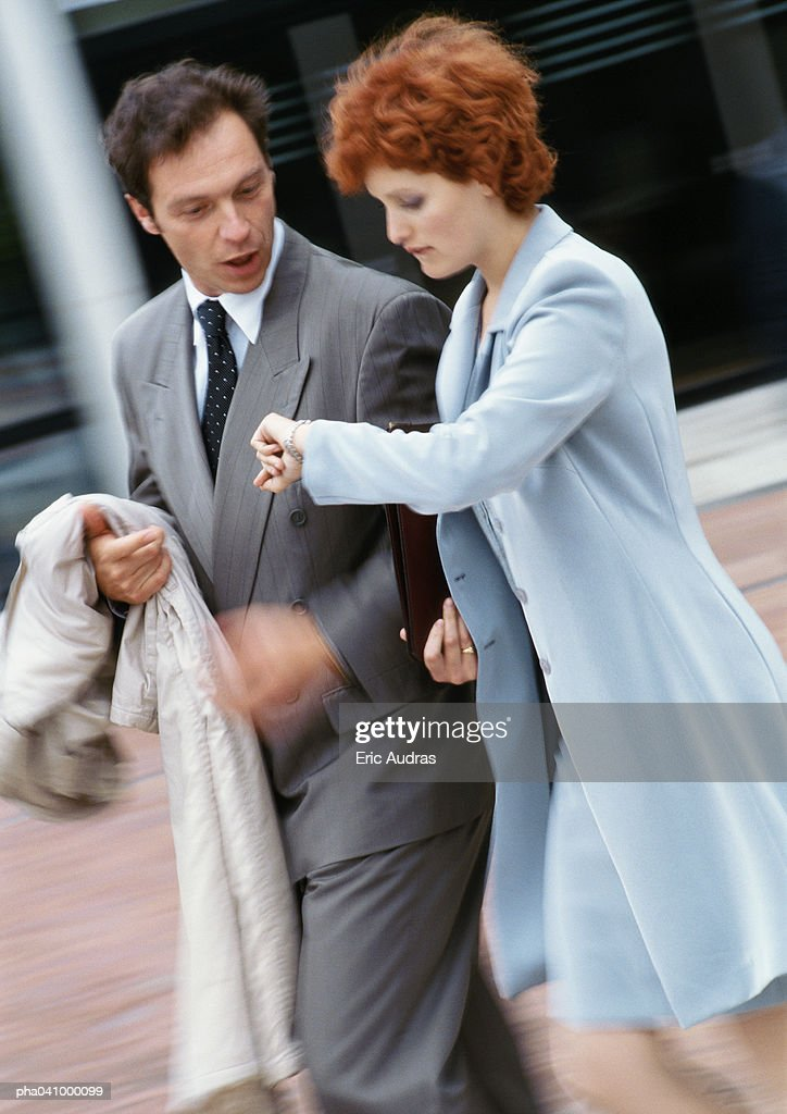 Businessman and businesswoman walking side by side outside, businessman looking at watch : Stockfoto