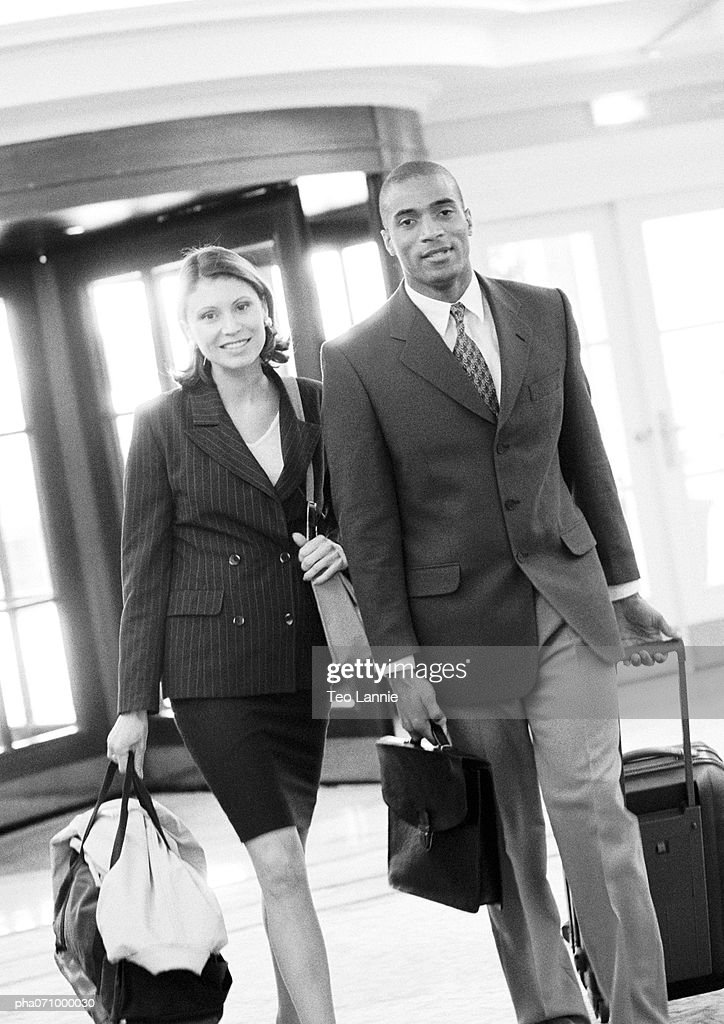 Businessman and businesswoman walking together inside building with luggage, b&w. : Stockfoto