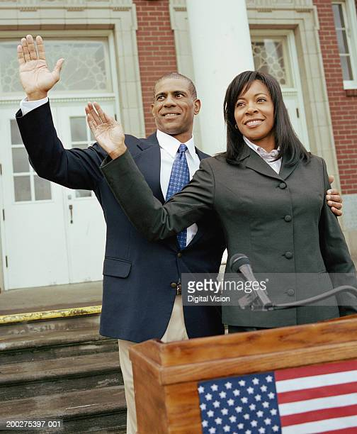 Businessman and businesswoman waving from podium outside building