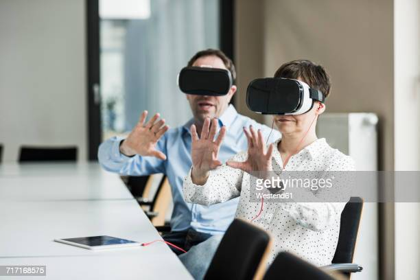 Businessman and businesswoman wearing VR glasses in office