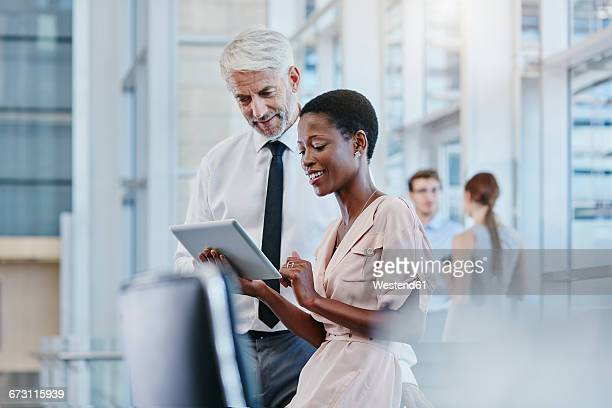 businessman and businesswoman with digital tablet - businesswear stock pictures, royalty-free photos & images