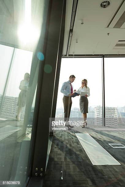 Businessman and businesswoman with documents in office
