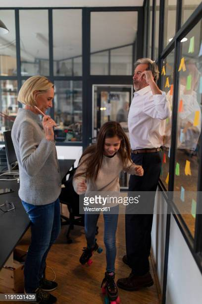 businessman and businesswoman with girl on roller skates in office - directrice stockfoto's en -beelden