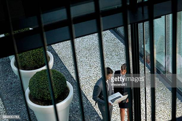 Businessman and businesswoman with laptop in an atrium