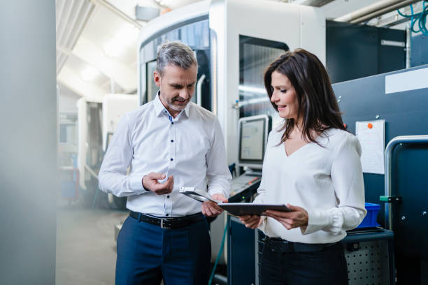 Businessman and businesswoman with product and tablet having a work meeting in a factory