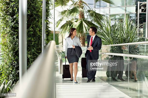 Businessman and businesswoman with suitcases