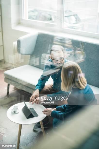 businessman and businesswoman with tablet discussing in office lounge - spiegelung stock-fotos und bilder